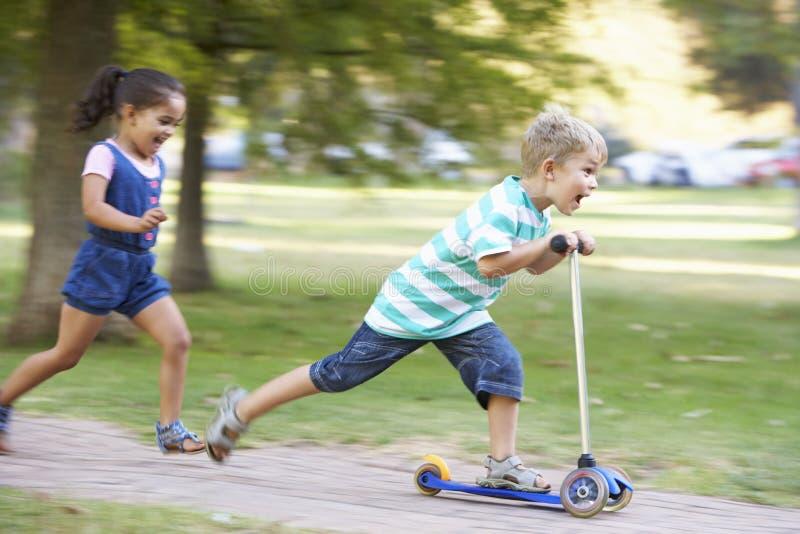 Den unga pojken på sparkcykeln parkerar in med systern fotografering för bildbyråer