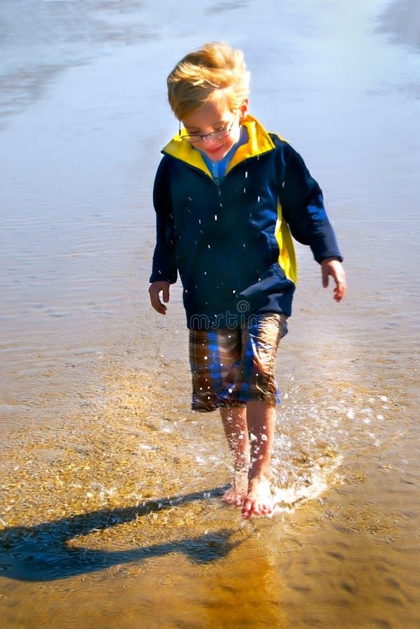 Den unga pojken plaskar i vattenlodlinje arkivbild