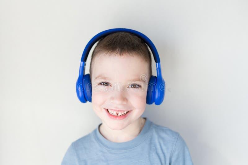 Den unga pojken ?r le och lyssna till musik i bl? h?rlurar som framme st?r av den vita v?ggen kopiera avst?nd arkivfoton