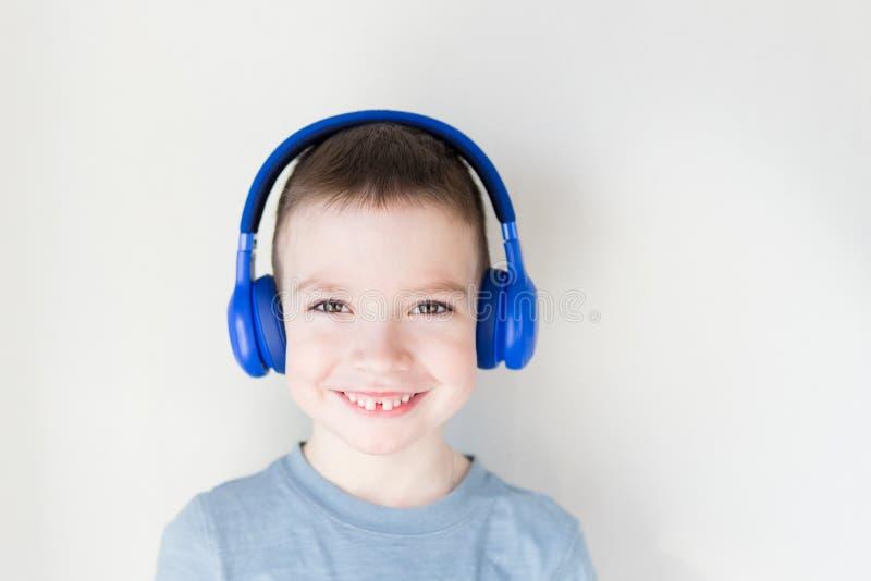 Den unga pojken ?r le och lyssna till musik i bl? h?rlurar som framme st?r av den vita v?ggen kopiera avst?nd fotografering för bildbyråer