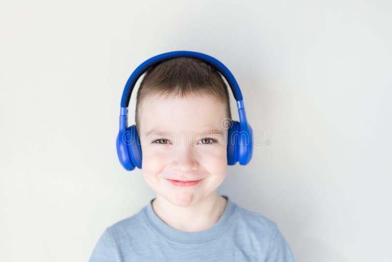 Den unga pojken ?r le och lyssna till musik i bl? h?rlurar som framme st?r av den vita v?ggen kopiera avst?nd royaltyfria bilder