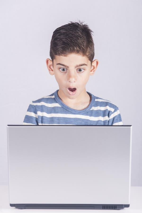 Den unga pojken reagerar, medan genom att använda en bärbar dator royaltyfria bilder