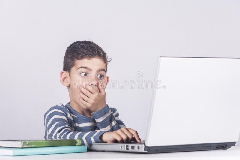 Den unga pojken reagerar, medan genom att använda en bärbar dator royaltyfri foto