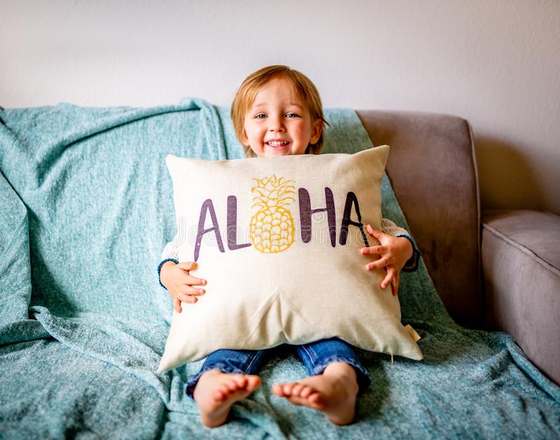 Den unga pojken sitter på soffan royaltyfria bilder