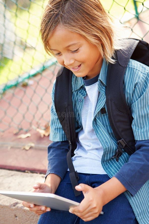 Den unga pojken som använder Digital minnestavlasammanträde parkerar in fotografering för bildbyråer