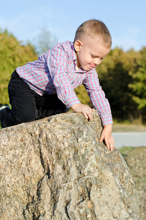Den unga pojken som clambering på, vaggar royaltyfri fotografi