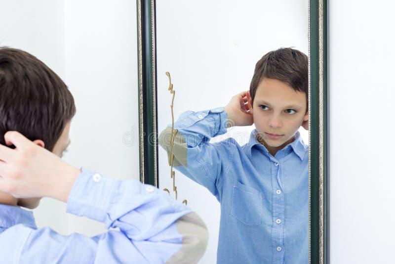 Den unga pojken som kammar hans hår avspeglar in arkivbild