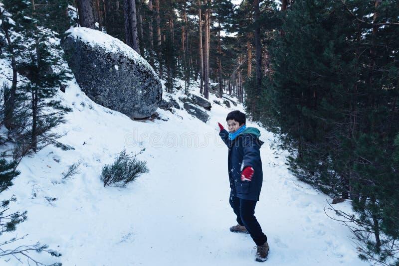 Den unga pojken som spelar med, kastar snöboll fotografering för bildbyråer