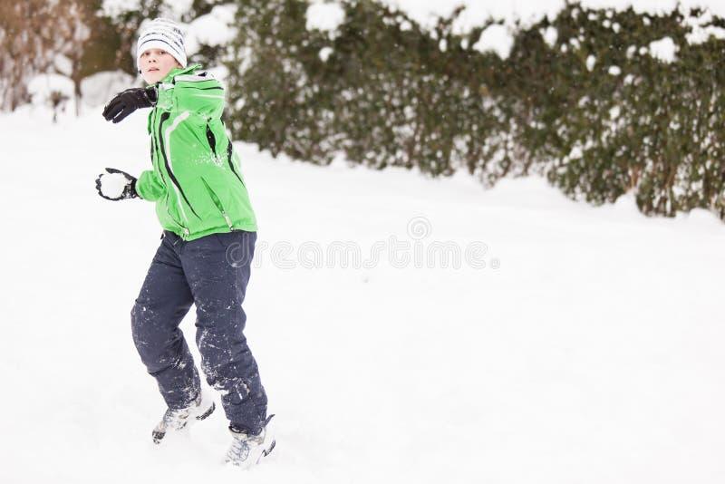 Den unga pojken som tycker om en vinter, kastar snöboll kamp royaltyfri foto