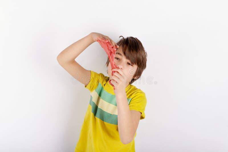 Den unga pojken som visar en röd slam, ser som smörja mellan hans händer arkivfoto