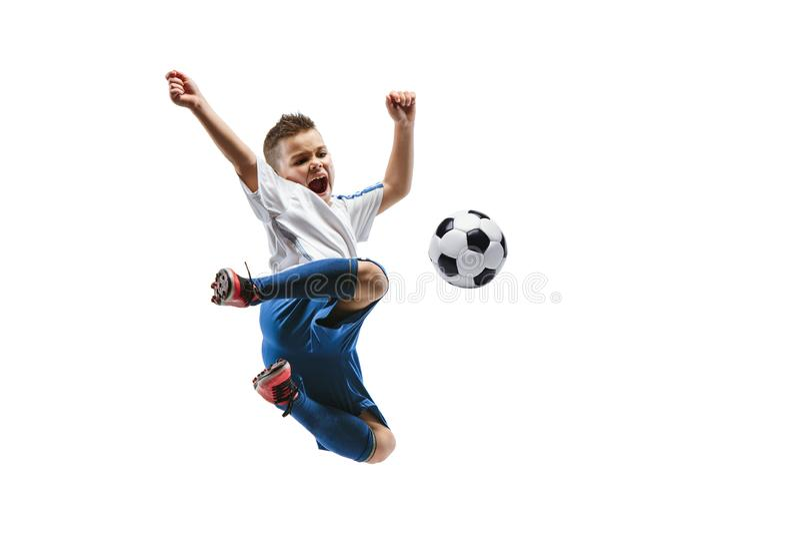 Den unga pojken sparkar fotbollbollen fotografering för bildbyråer