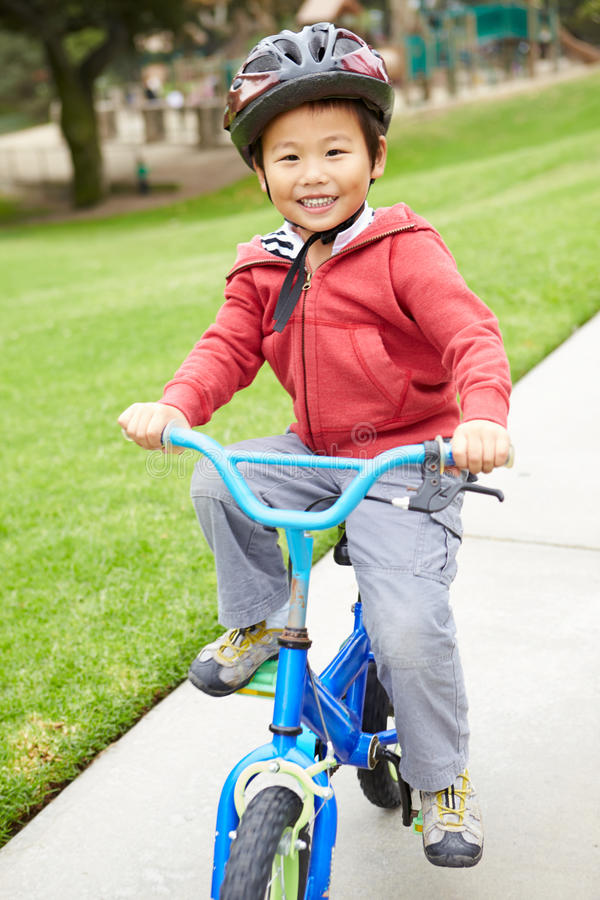Den unga pojkeridningcykeln parkerar in arkivbild