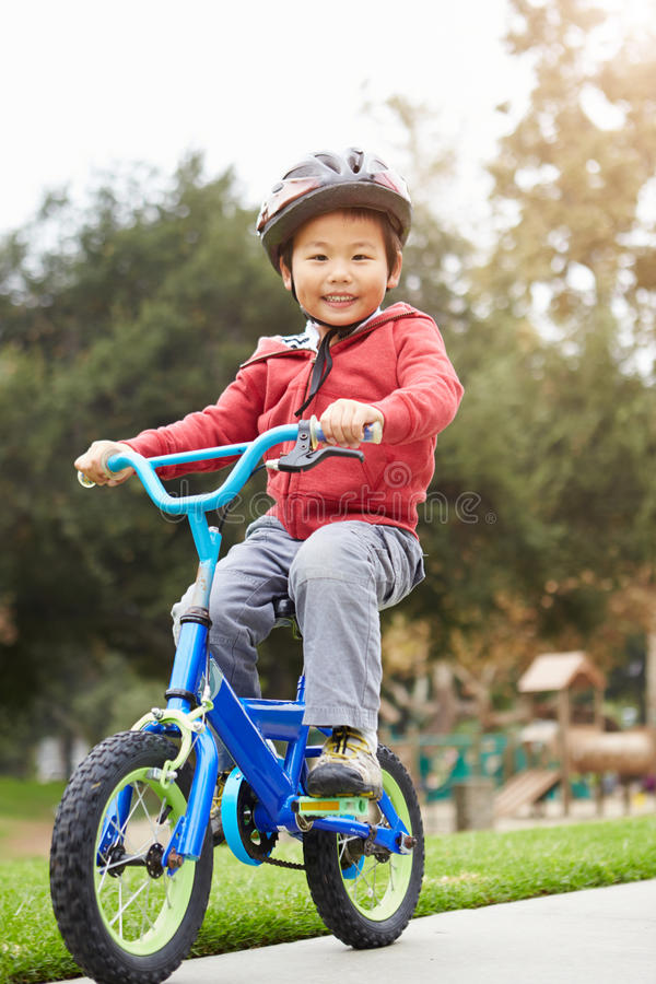 Den unga pojkeridningcykeln parkerar in arkivfoton
