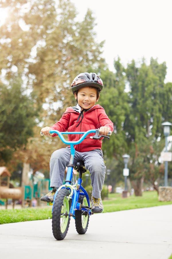 Den unga pojkeridningcykeln parkerar in royaltyfria bilder