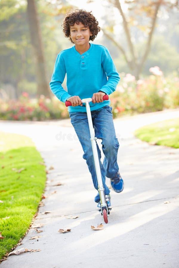 Den unga pojkeridningsparkcykeln parkerar in arkivfoto