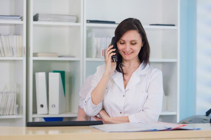 Den unga praktikerdoktorn som arbetar på klinikmottagandeskrivbordet, svarar hon påringning- och planlagdtidsbeställningar arkivfoto