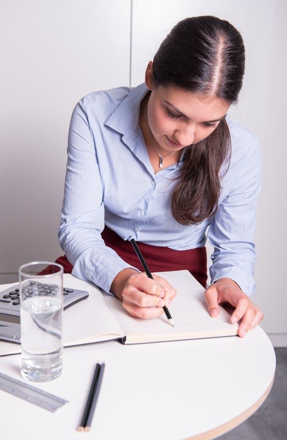 Den unga professionelln skriver hennes idé i öppen anteckningsbok fotografering för bildbyråer