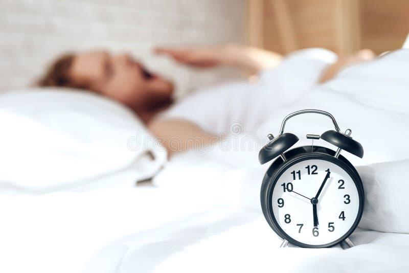 Den unga röda haired grabben vaknar upp att gäspa i säng royaltyfri bild