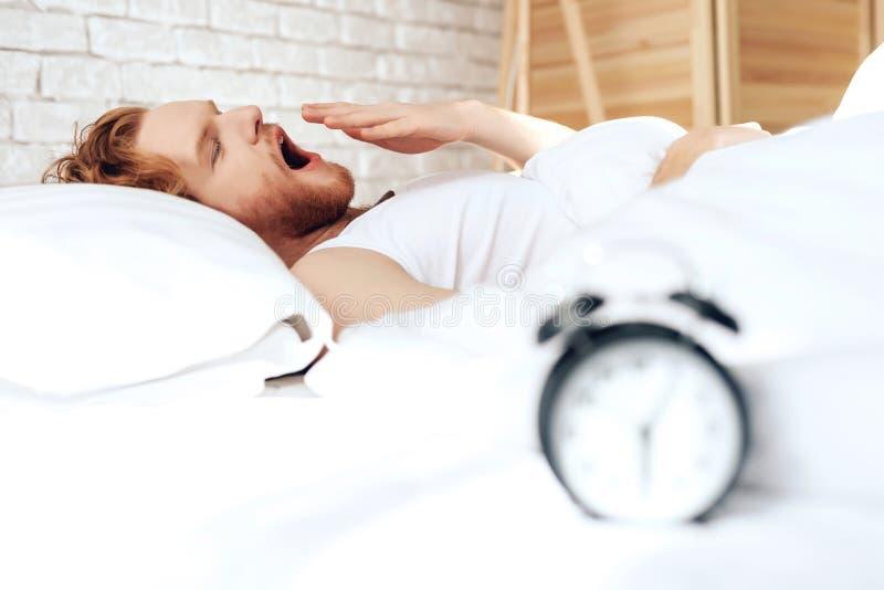 Den unga röda haired grabben vaknar upp att gäspa i säng arkivfoton