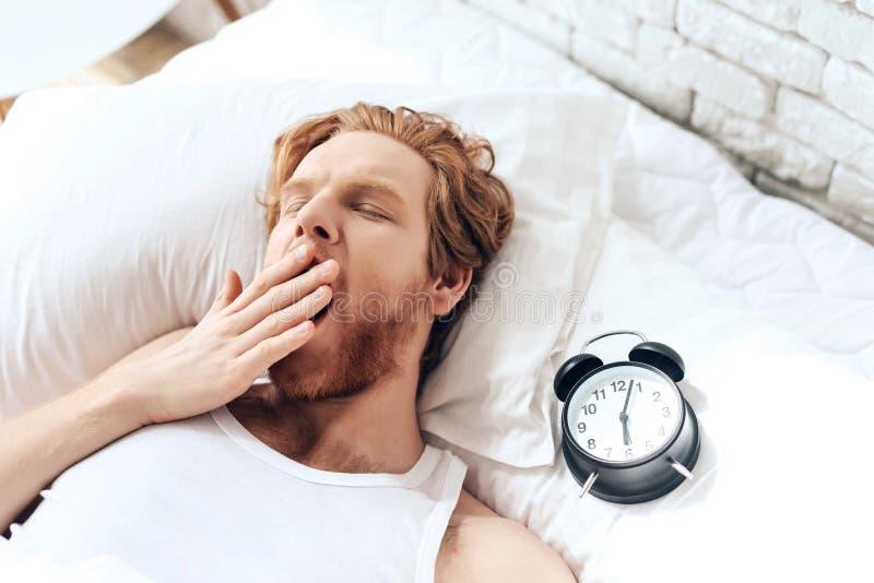 Den unga röda haired mannen gäspar att ligga i säng royaltyfri foto