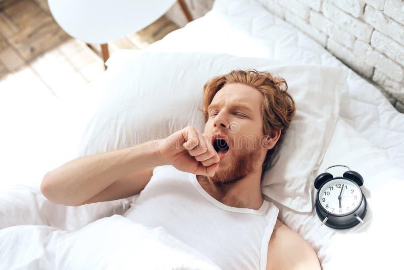 Den unga röda haired mannen gäspar att ligga i säng royaltyfria foton