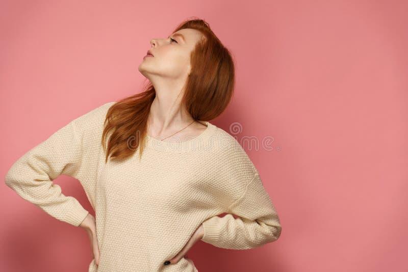 Den unga rödhårig mankvinnan kastar hennes huvud proudly med hennes händer på hennes höfter arkivfoto