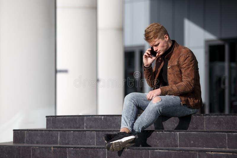 Den unga rödhårig manmannen i brunt omslag talar vid telefonen, medan sitta på moment utomhus royaltyfri fotografi