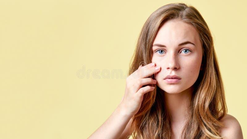 Den unga rödhårig mantonåringen med själv utfärdar att se in i spegeln Flicka med låg självaktning som kontrollerar hennes hud arkivbilder