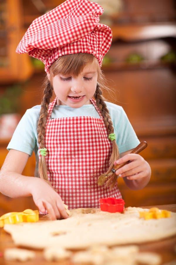 Den unga rödhåriga flickan gör kakor i kök fotografering för bildbyråer