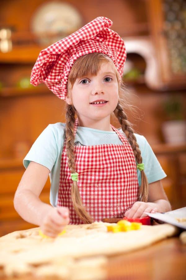 Den unga rödhåriga flickan gör kakor i kök royaltyfria foton