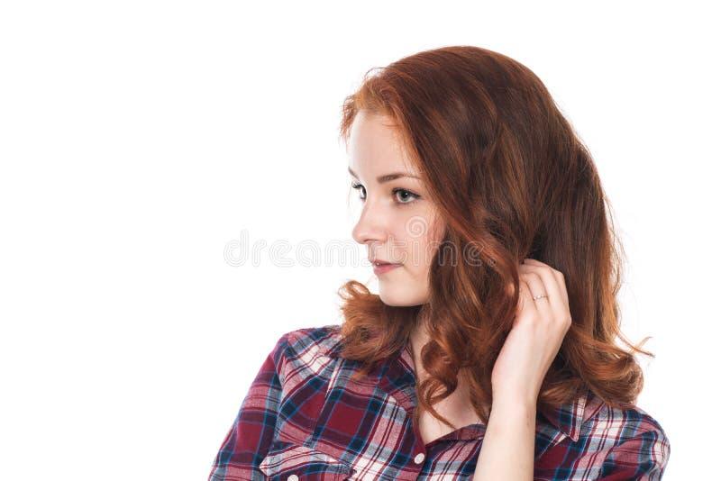 Den unga rödhåriga flickan i en plädskjorta ser bort royaltyfri fotografi