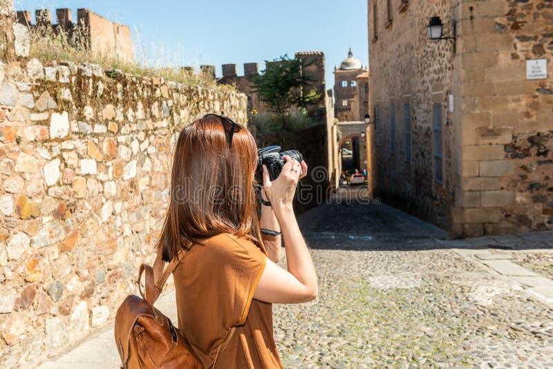 Den unga rödhåriga turisten med en ryggsäck tar fotografier av de smala gatorna av den gamla staden av Caceres royaltyfria foton