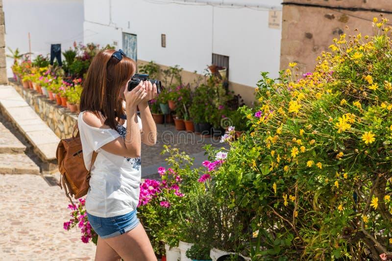 Den unga rödhåriga turisten tar fotografier av blommorna av den gamla judiska fjärdedelen av Caceres royaltyfria foton