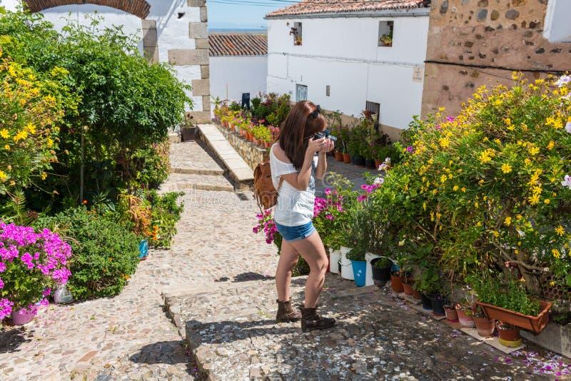 Den unga rödhåriga turisten tar fotografier av blommorna av den gamla judiska fjärdedelen av Caceres arkivbilder