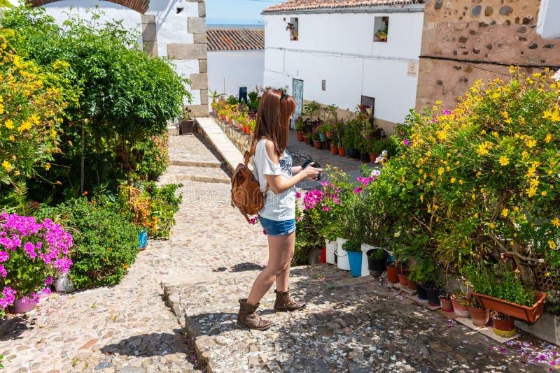 Den unga rödhåriga turisten tar fotografier av blommorna av den gamla judiska fjärdedelen av Caceres arkivfoto