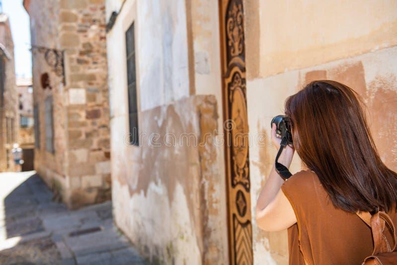 Den unga rödhåriga turisten tar fotografier med hennes kamera av de smala gatorna av den gamla staden av Caceres royaltyfri fotografi