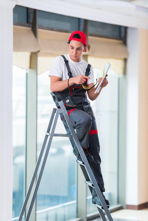 Den unga repairmanen som kontrollerar teckningarna, innan att starta arbetet fotografering för bildbyråer
