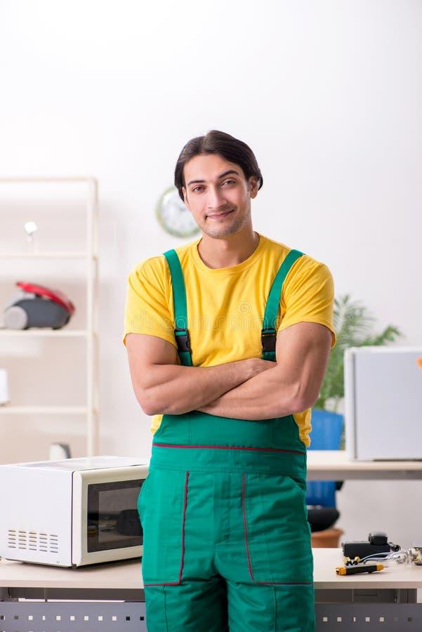 Den unga repairmanen som reparerar mikrov?gen i servicemitt royaltyfria bilder