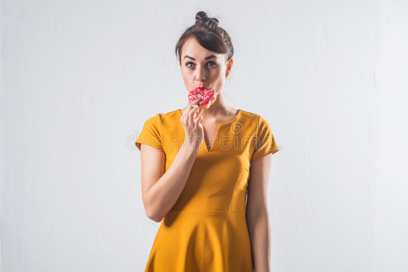 Den unga roliga brunettmodellen med donuts som poserar studion, sköt på vit bakgrund som inte isolerades arkivfoto