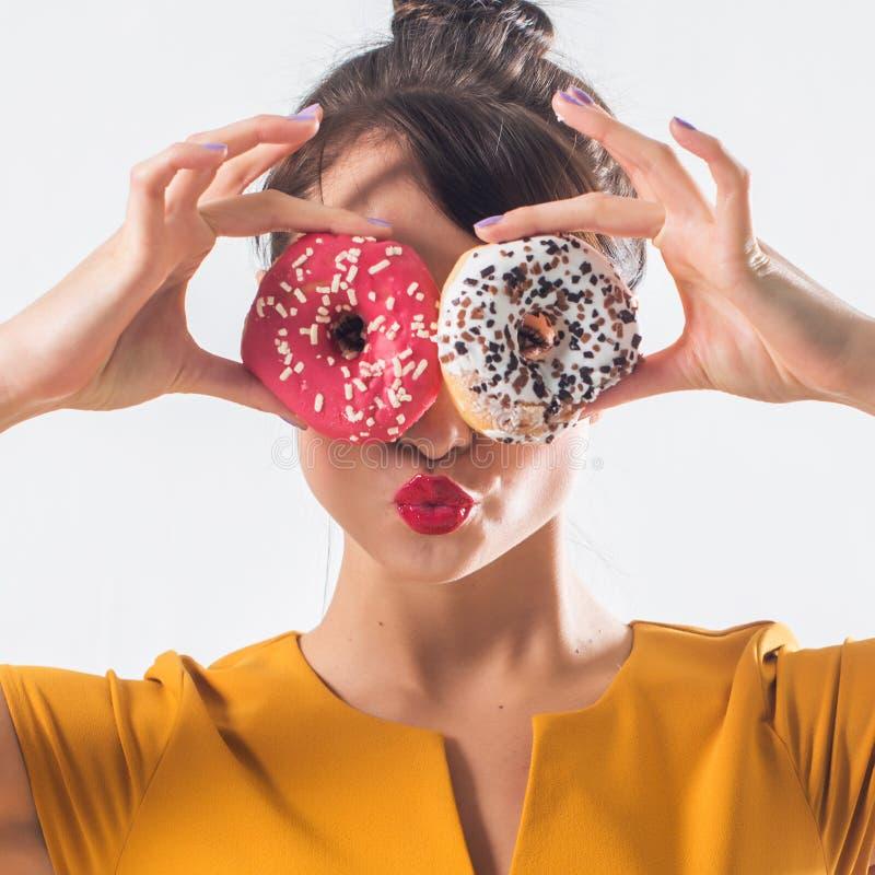 Den unga roliga brunettmodellen med donuts som poserar studion, sköt på vit bakgrund som inte isolerades royaltyfri bild
