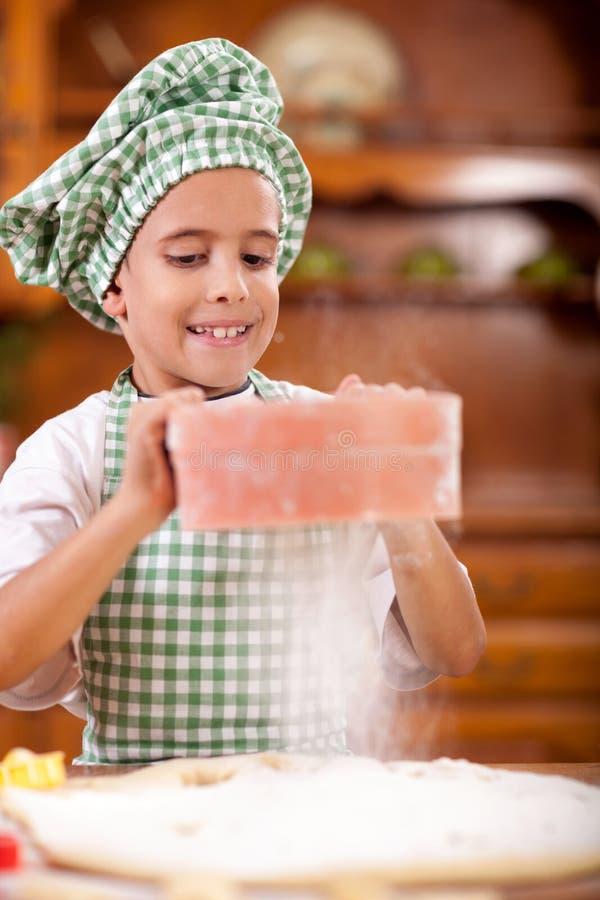 Den unga roliga pojken strilade mjöl över deg i köket arkivfoto