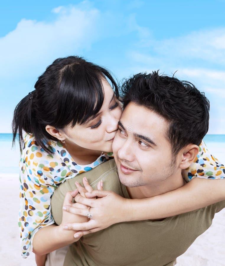 Romantiker kopplar ihop att krama på stranden arkivfoto