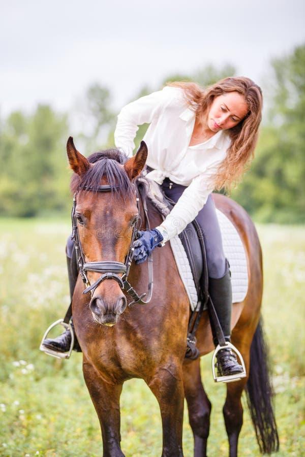 Den unga ryttareflickan böjde till hästen för att ge en komplimang royaltyfria bilder