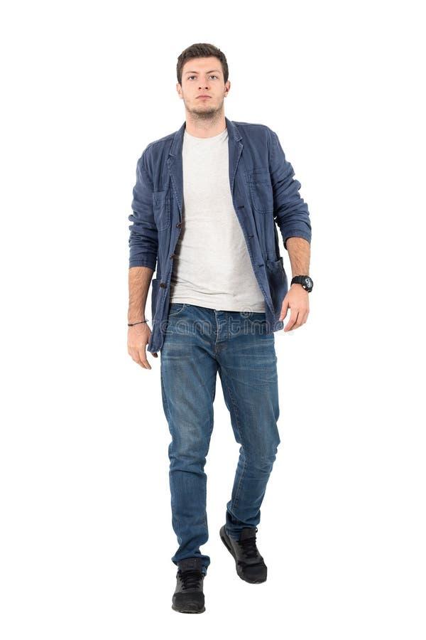 Den unga säkra mannen i grov bomullstvill knäppte upp skjortan och jeans som går in mot kamera arkivfoto