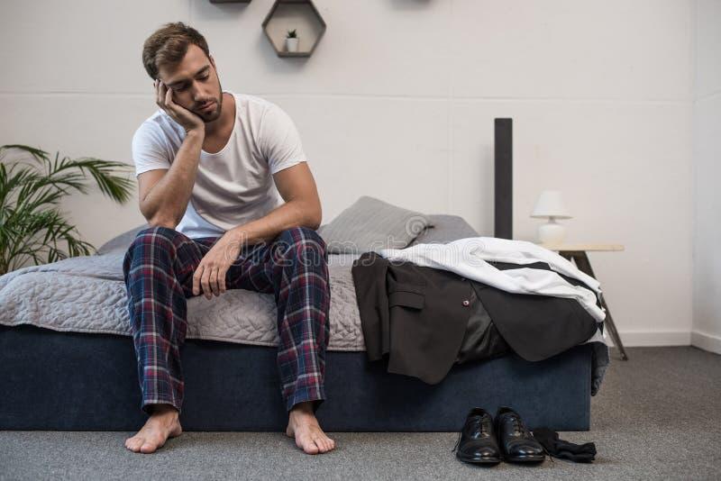 Den unga sömniga mannen i hem beklär sammanträde på säng, når han har vaknat upp royaltyfri fotografi