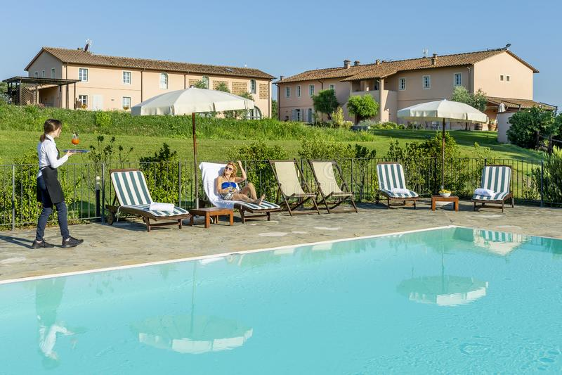 Den unga servitrins tjänar som en poolsidecoctail till en kund som sitter på en dagdrivare i en semesterort i bygden av Pisa, Ita fotografering för bildbyråer