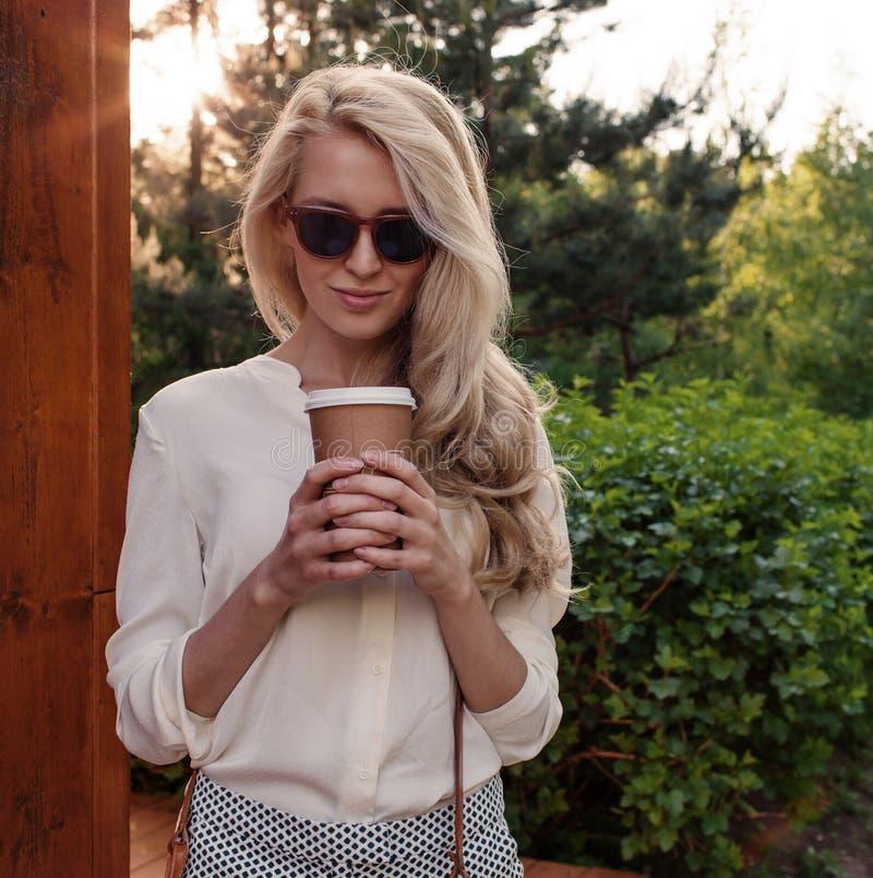 Den unga sexiga blonda flickan med långt hår i solglasögon som rymmer en kopp kaffe, har det roliga och bra lynnet som in camera  arkivbilder