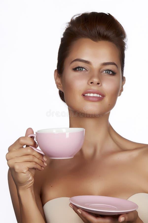 Den unga sexiga härliga kvinnan med mörkt hår valde upp att rymma en keramisk kopp- och tefatgräns - rosa färger dricker te eller royaltyfri fotografi