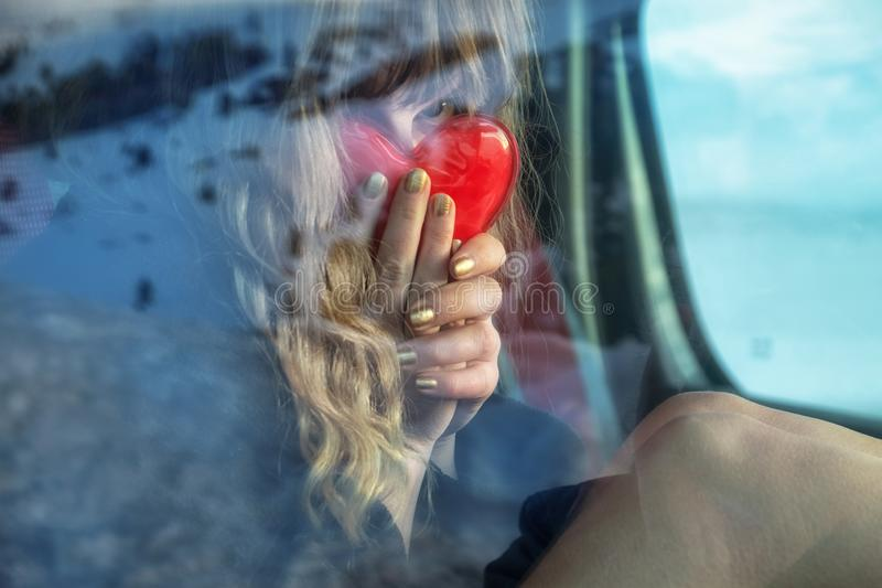 Den unga sexiga kvinnan med blont lockigt hår sitter i bilen i vinter och döljer framsidan bak en hjärta som en handvärmeapparat royaltyfri foto