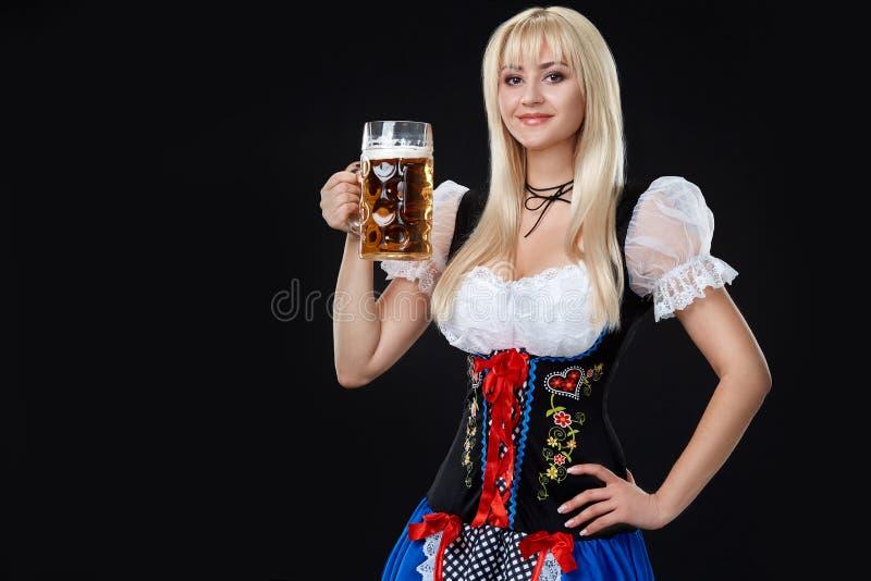 Den unga sexiga kvinnan som bär en dirndl med öl, rånar på svart bakgrund royaltyfri fotografi